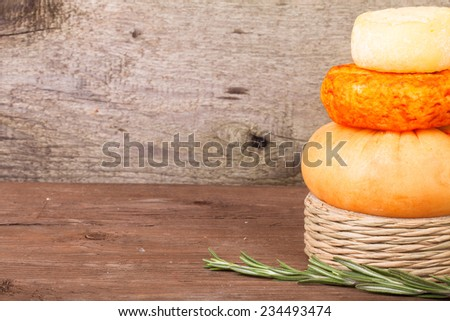 several varieties of cheese and a sprig of rosemary on an old wooden table. background - stock photo