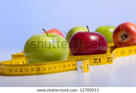 Several varieties of fresh apples on a blue background with a tape measure.  Dieting and healthy eating concept.  Includes copy space