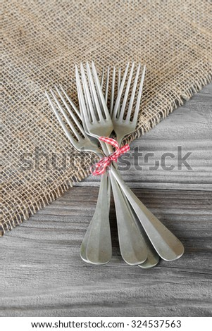 Several vintage forks tied with checkered red and white ribbon on the old wooden table