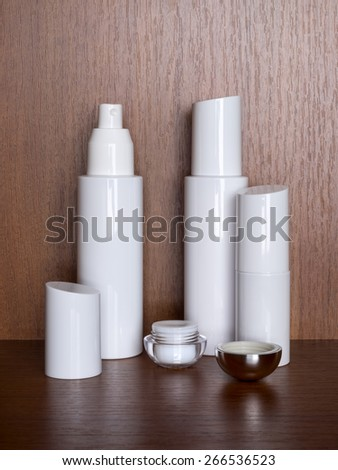 Several white bottles with cosmetic on a wooden table