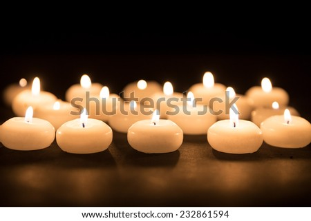Several white candles with selective focus on a black background - stock photo