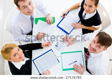 Several white collar workers looking upwards at camera from their workplace - stock photo