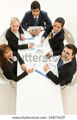 Several white collar workers looking upwards at camera with happy smiles