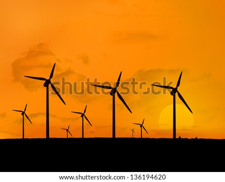 Several wind turbines with a sunset in line