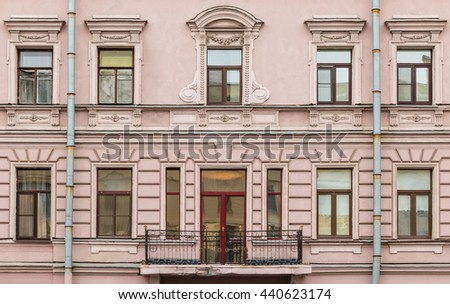 Several windows in a row and balcony on facade of urban apartment building front view, St. Petersburg, Russia