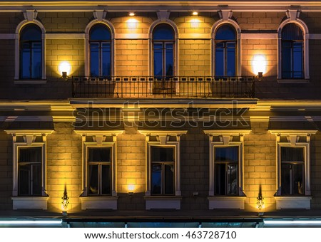 Several windows in a row and balcony on night illuminated facade of urban office building front view, St. Petersburg, Russia