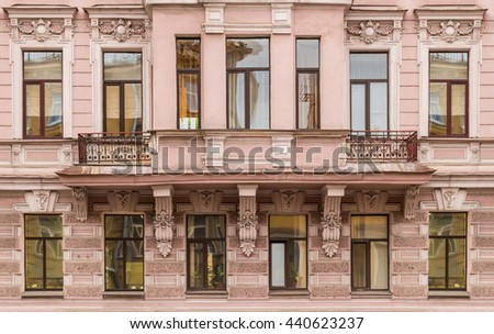 Several windows in a row and bay window on facade of urban apartment building front view, St. Petersburg, Russia