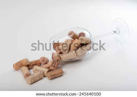 "Several Wine Corks coming out of a Wineglass on a white background. You can read "" Mis en Bouteille"" (filled in the bottle or bottled) or the Origin of the Wine and or the Vintage on them. - stock photo"