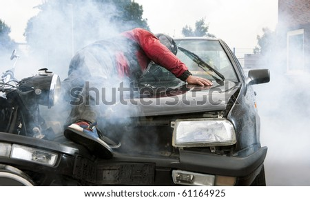 Severe accident between a motorcyclist and a car, injuring both drivers and causing a lot of damage - stock photo