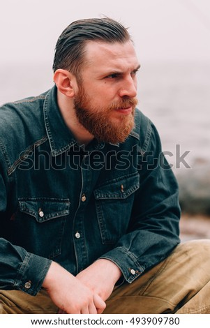 Severe bearded man about something thoughtful. bearded hipster on the beach