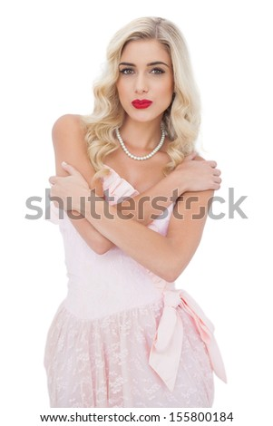 Severe blonde model in pink dress posing holding her shoulders and looking at camera on white background - stock photo