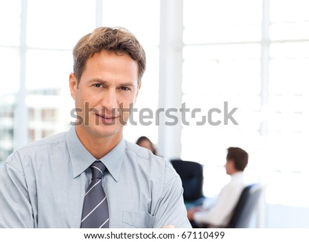 Severe businessman standing in front of his team while working at a table in the background