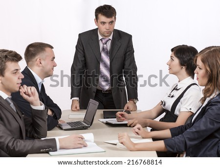 Severe corporate manager is observing his business team.