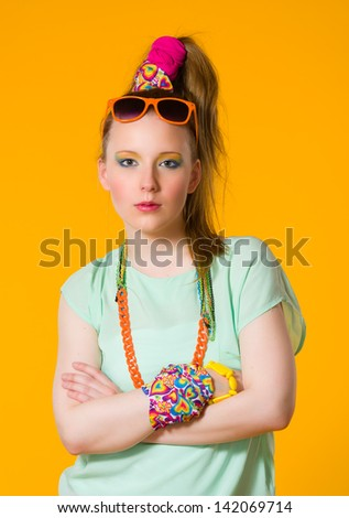 Severe girl with colorful clothes, yellow background