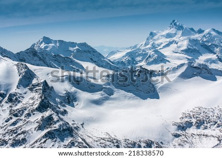 Severe mountains peaks covered by snow  - stock photo