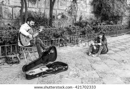 Sevilla, Spain - 23 March 2014: Street musician performs romantic songs on the street in Sevilla, Spain