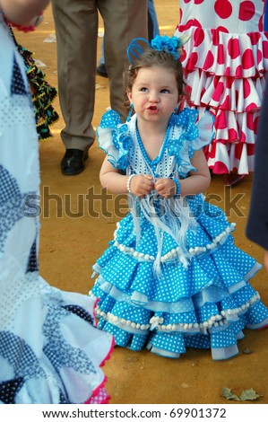 SEVILLE - APRIL 28: Even the youngest girls dress traditional flamenco dresses during the Feria de Abril on April 28, 2009 in Seville, Spain. Unidentified little girl - stock photo