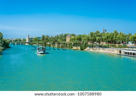 SEVILLE, ES - JULY 31, 2017: Views from the Guadalquivir River as a tourist cruise passes through Seville in Andalusia, Spain.