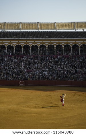 SEVILLE - MAY 4: A bullfighter performs before a sold-out crowd in the Plaza de Toroes de Sevilla May 4, 2011 in Seville, Spain. - stock photo