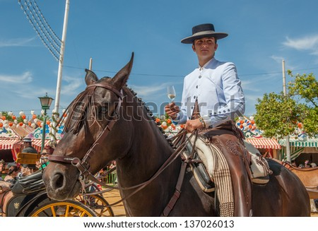 SEVILLE, SPAIN - APR, 25: Horse rider with a glass of manzanilla at the Seville's April Fair on April, 25, 2012 in Seville, Spain