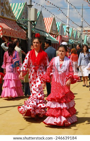 SEVILLE, SPAIN - APRIL 12, 2008 - Girls walking alongside Casitas in traditional dress at the Seville Fair, Seville, Seville Province, Andalusia, Spain, Western Europe, April 12, 2008. - stock photo