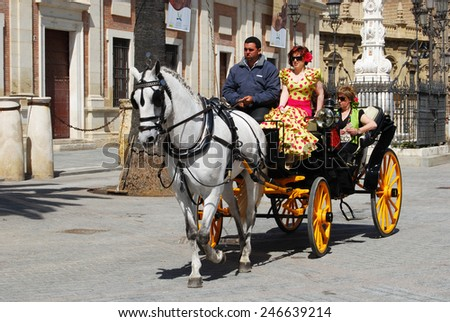 SEVILLE, SPAIN - APRIL 12, 2008 - Spanish women in traditional dress travelling in a horse drawn carriage by the Cathedral, Seville, Seville Province, Andalusia, Spain, Western Europe, April 12, 2008. - stock photo