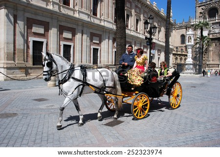 SEVILLE, SPAIN - APRIL 12, 2008 - Spanish women in traditional dress travelling in a horse drawn carriage outside the Cathedral, Seville, Seville Province, Andalusia, Spain, April 12, 2008. - stock photo