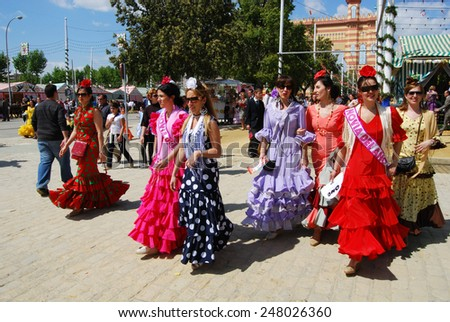 SEVILLE, SPAIN - APRIL 12, 2008 - Spanish women in traditional dress walking along the street at the Seville Fair, Seville, Seville Province, Andalusia, Spain, Western Europe, April 12, 2008. - stock photo