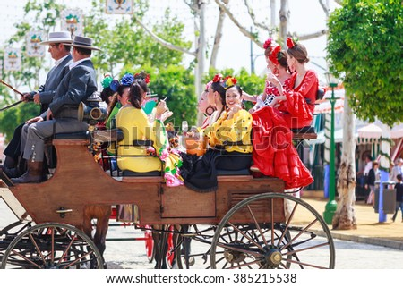 SEVILLE, SPAIN - APRIL 28, 2015: Young and beautiful women on a horse drawn carriage during the the April Fair of Seville on April, 28, 2015 in Seville, Spain - stock photo