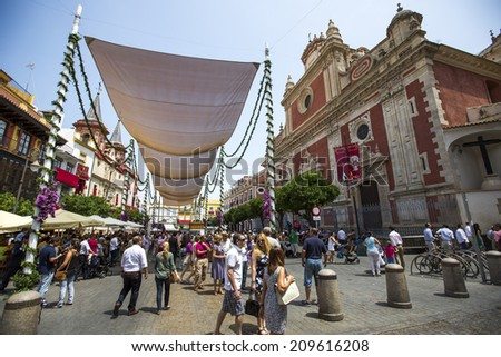 Seville, Spain - June 18: People on the streets of Seville, Spain during the procession on June 18, 2014. The procession is a religious event, not a holiday. - stock photo