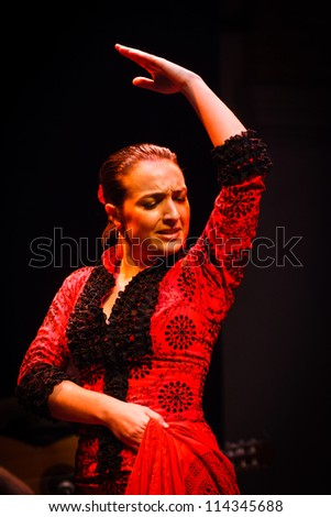 SEVILLE, SPAIN - MAY 1: Flamenco dancer performs traditional step in classical red dress costume on may 1, 2010 in Seville, Spain. It is very popular in Tucson Arizona's Flamenco Festival