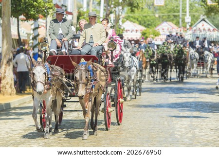 SEVILLE, SPAIN-MAY 8: People mounted on a carriage horse in fair Seville, on May 8, 2014 in Seville. - stock photo