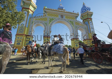 SEVILLE, SPAIN-MAY 8: People mounted on horse in the Cover of the Seville Fair, on May 8, 2014 in Seville. - stock photo