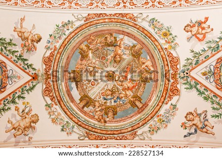 SEVILLE, SPAIN - OCTOBER 28, 2014: The fresco of angels with the insignia of pope on the ceiling in church Hospital de los Venerables Sacerdotes by Juan de Valdes Leal (1622 - 1690).  - stock photo