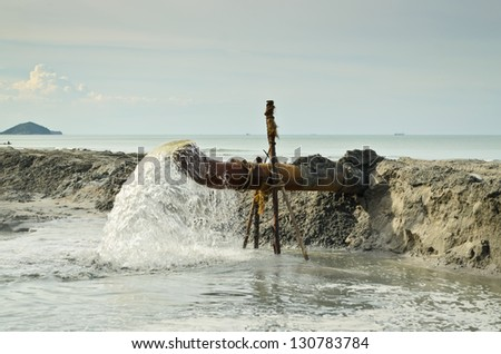 Sewage from the sewer pollutes at shore - stock photo