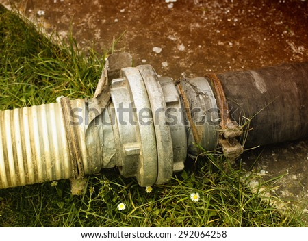 Sewage pipes for extracting septic water from cesspit in courtyard - stock photo
