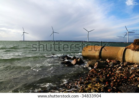sewage waste pipe and offshore wind mills or turbines. coast with pollution and envirnmental friendly green energy production - stock photo