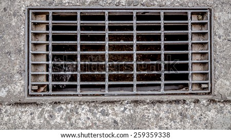Sewer cover or storm drain in street - stock photo