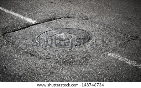 Sewer manhole cover on asphalt road with white road marking - stock photo