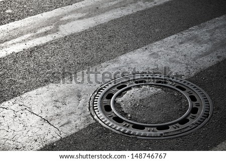 Sewer manhole cover on dark asphalt road with pedestrian crossing marking