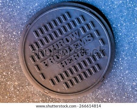 sewer manhole cover surrounded by an asphalt street - stock photo