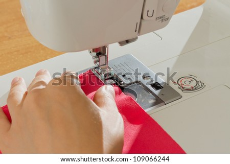sewing a pink dress on a sewing machine