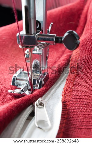 sewing a white zipper on a sewing machine. sewing process - stock photo