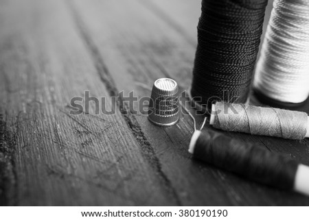 Sewing accessories: bobbins of thread, needle, thimble on wooden table. Black and white photo. Tailoring and sewing concept. - stock photo