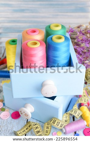 Sewing Accessories in wooden boxes on table on light blue background - stock photo