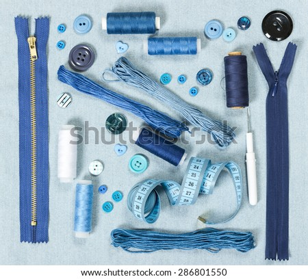 Sewing accessories on blue denim background. Zippers, buttons, thread, measuring tape. - stock photo