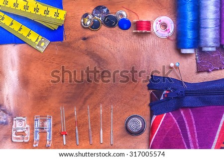 sewing accessories: pin, thimble, thread, bobbin, needle, zip, textile, foot, measure tape, button on wooden table - stock photo