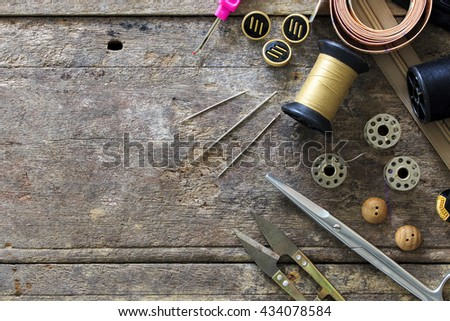 Sewing accessories.  scissors, needle, thimble on wooden table background, over light - stock photo