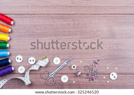 Sewing accessories. Spools of thread with different colors of rainbow, scissors, buttons, measuring tape and accessories for needlework on wooden background. Set for handmade top view - stock photo