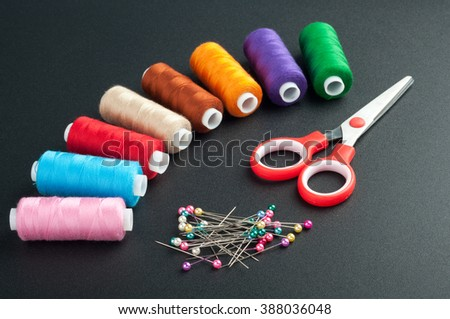 Sewing accessories. Spools with various colors of thread, scissors and pins on dark background.